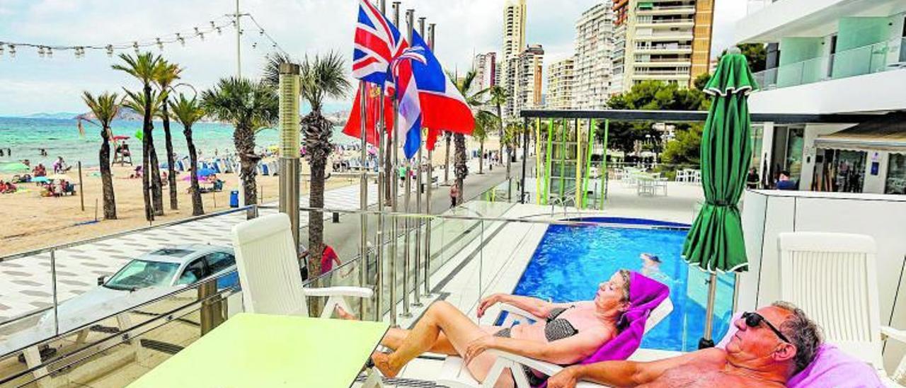 Dos turistas toman el sol en la piscina de un hotel ubicado en la primera línea de la playa de Levante, en Benidorm, esta semana.    DAVID REVENGA
