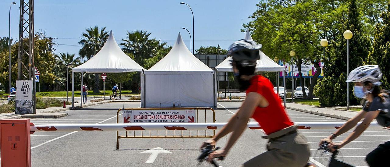 .Ciclistas pasan ante una carpa para la prueba de la PCR en el Hospital de Sant Joan.    HÉCTOR FUENTES