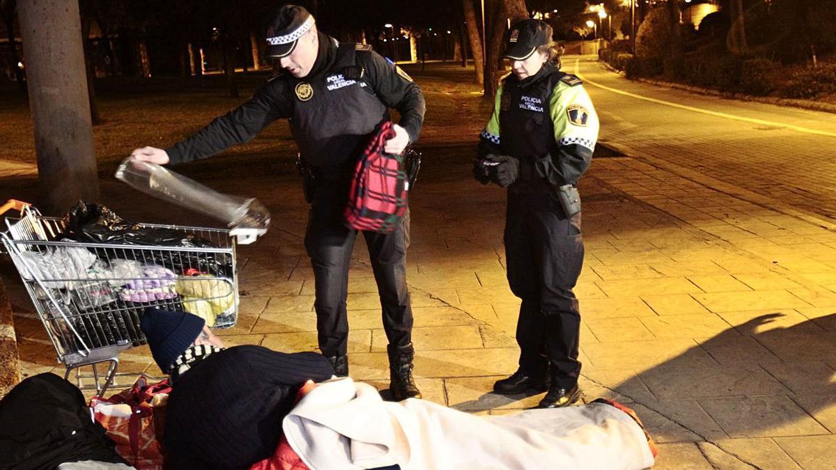 Dos agentes de policía entregan mantas a una persona sin hogar, en una foto de archivo.   EDUARDO RIPOLL