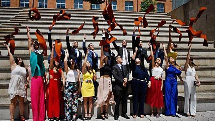 Un grupo de alumnos graduados en el Campus Universitario Viriato lanzan al aire sus bandas.