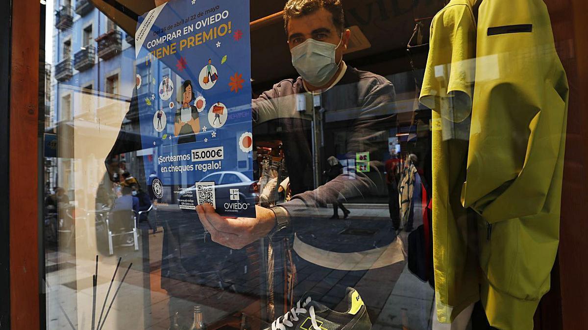 Ángel Blanco coloca el cartel de la campaña electoral municipal en el escaparate de su tienda de ropa.  |  Luisma Murias