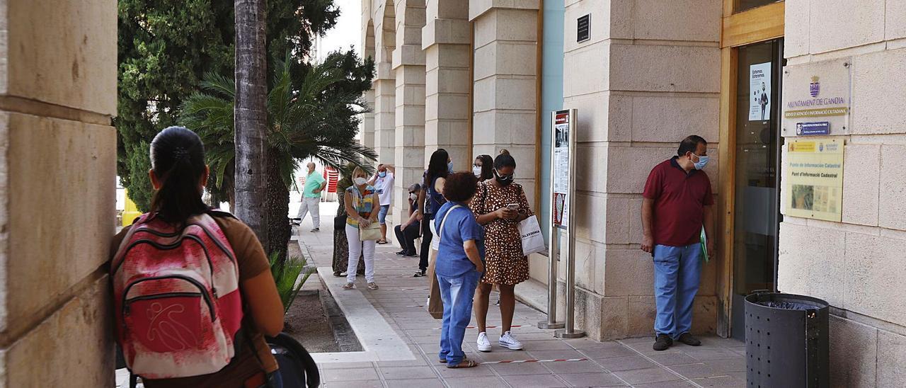 Varias personas hacen cola ante el Ayuntamiento de Gandia con sus preceptivas mascarillas.   LEVANTE-EMV