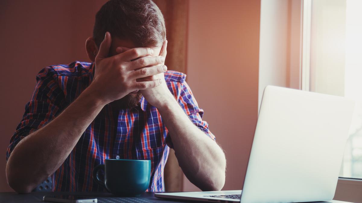 Un hombre se muestra cansado mientras trabaja delante del ordenador