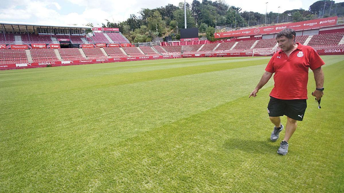 Un treballador del Girona revisant la gespa de l'estadi de Montilivi