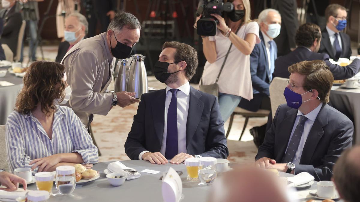 La presidenta de la Comunidad de Madrid, Isabel Díaz Ayuso; el presidente del Partido Popular, Pablo Casado, y el alcalde de Madrid, José Luis Martínez-Almeida, conversan durante un desayuno informativo.