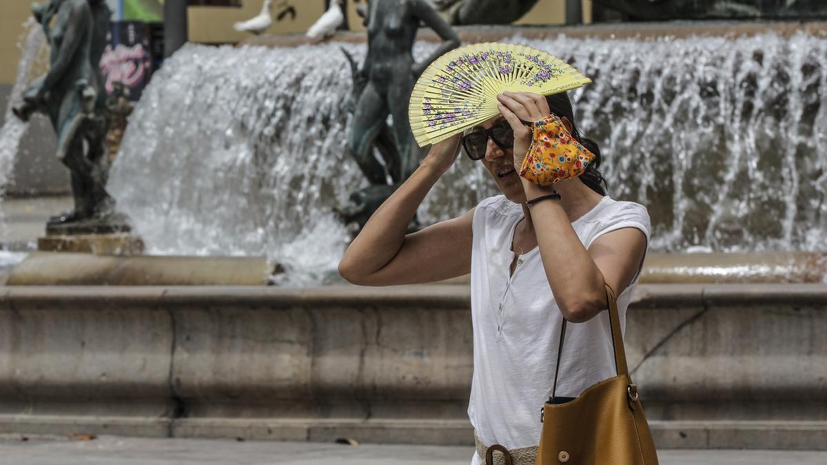 Una mujer se tapa la cabeza con un abanico para guarecerse de las altas temperaturas cerca de una céntrica fuente de a 12 de julio de 2021, en Valencia, Comunidad Valenciana (España).