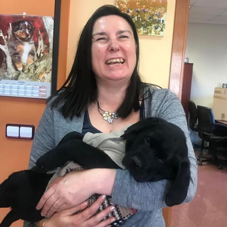 María Jesús Varela, con un cachorro de labrador negro entre sus brazos, en las instalaciones de la FOPG.
