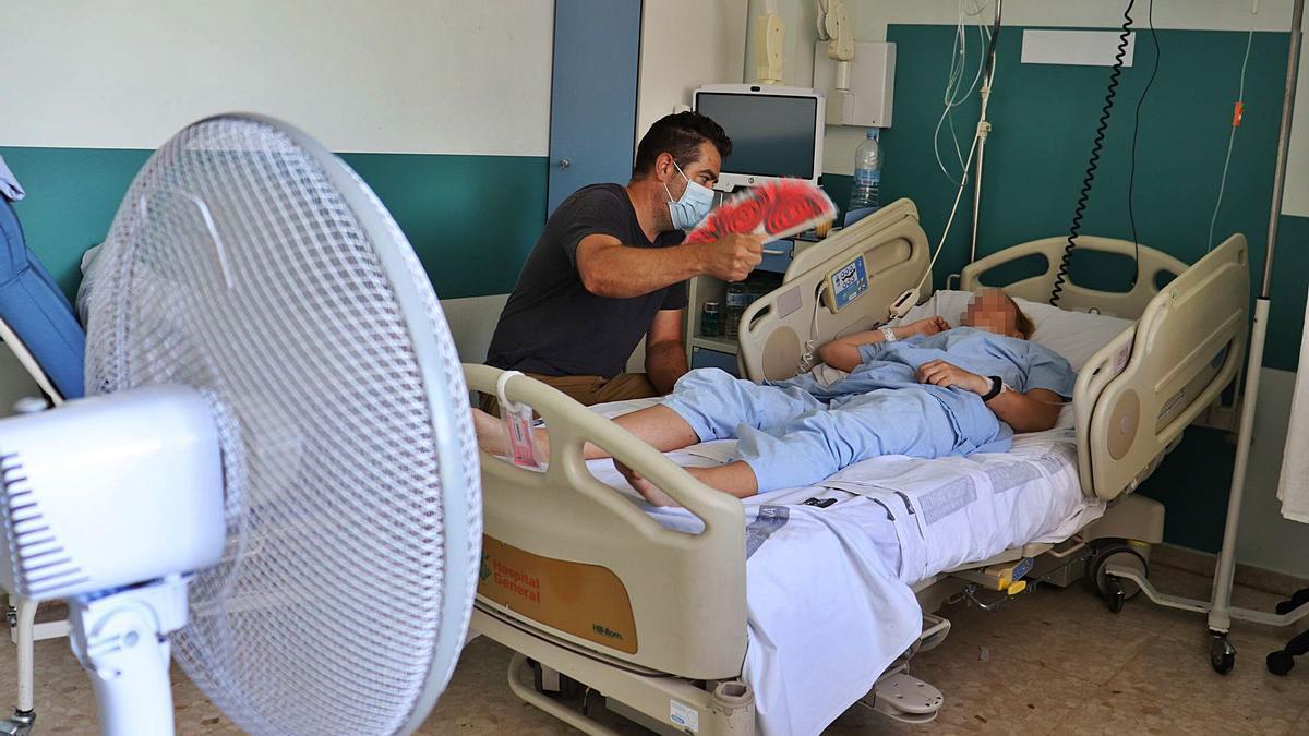 Pacientes y familiares tratan de combatir las altas temperaturas con ventiladores que se han traído de casa y abanicos. | I. CABANES