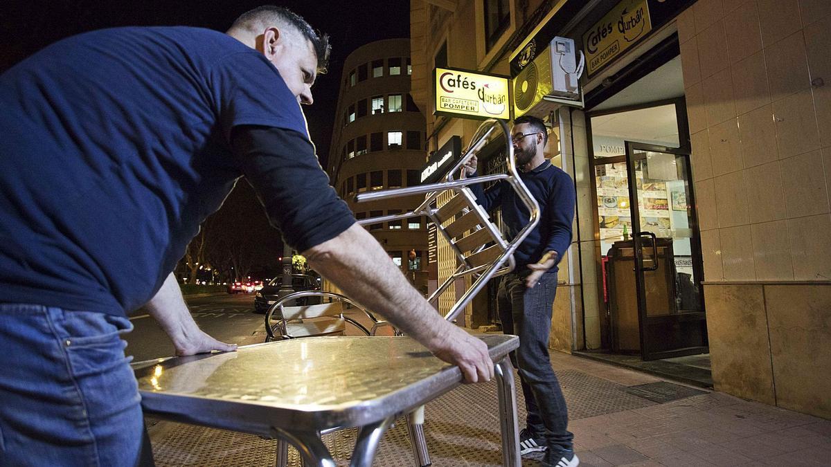 Dos trabajadores recogen  las mesas de su terraza  antes del cierre.  F bUSTAMANTE