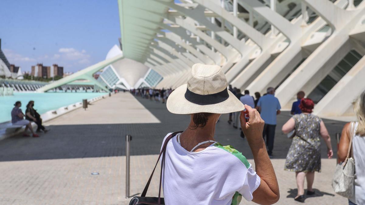 Una mujer se protege del sol y del calor este jueves en el vacunódromo de la Ciudad de las Artes.