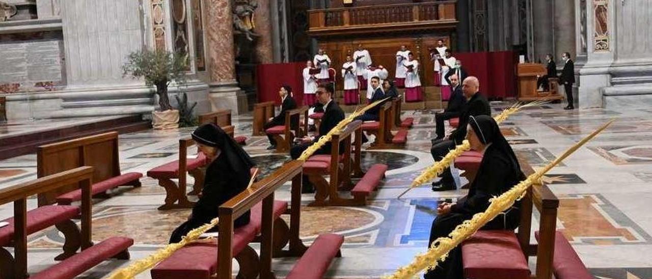 La basílica de San Pedro casi vacía, y a la derecha, el Pontífice bendice los ramos.