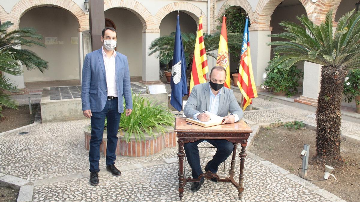 El conseller de Vivienda firma en el libro de honor del ayuntamiento en la visita que realizó en octubre