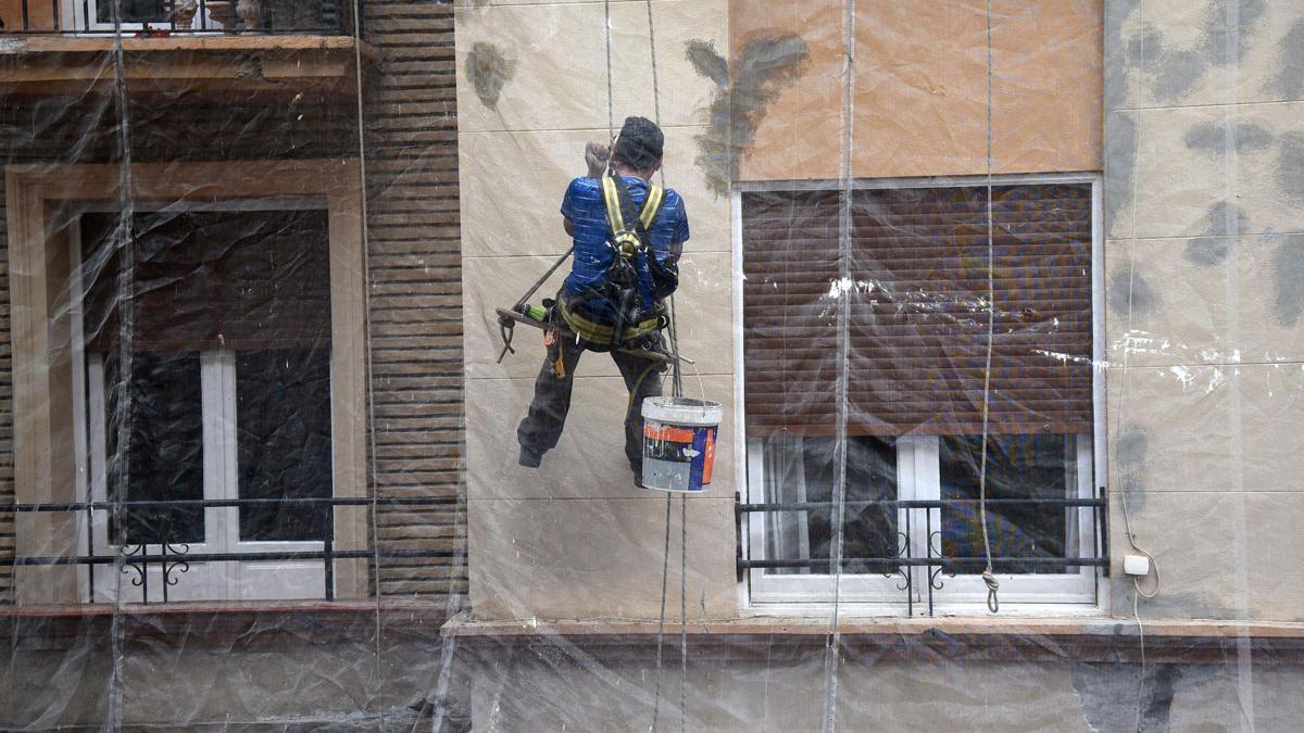 Trabajador en la fachada de un edificio en rehabilitación