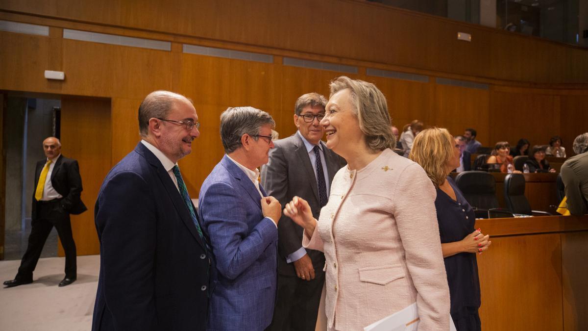 El presidente aragonés, Javier Lambán, y la expresidenta, Luisa Fernanda Rudi, se saludan en las Cortes de Aragón.