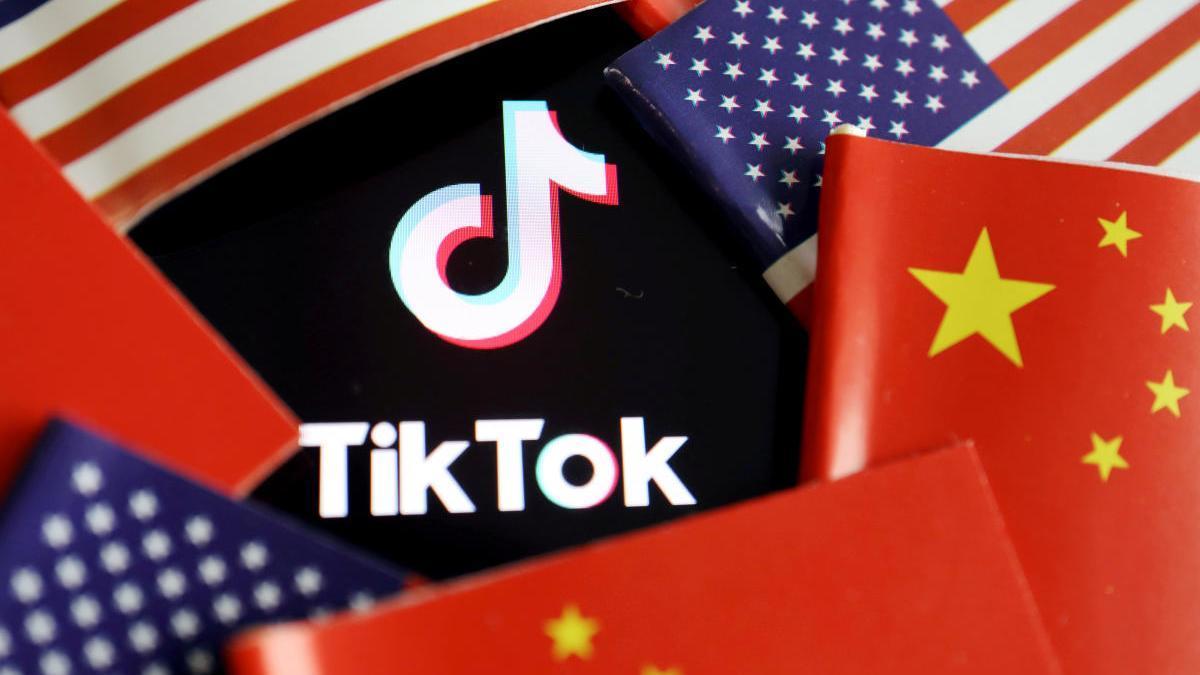 El logo de TikTok entre banderas de China y EEUU
