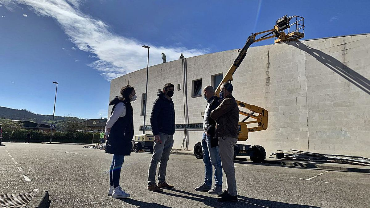 A la derecha, Jesús Abad, con personal municipal, ayer, en las obras de impermeabilización del techo del polideportivo de El Berrón.   A. I.