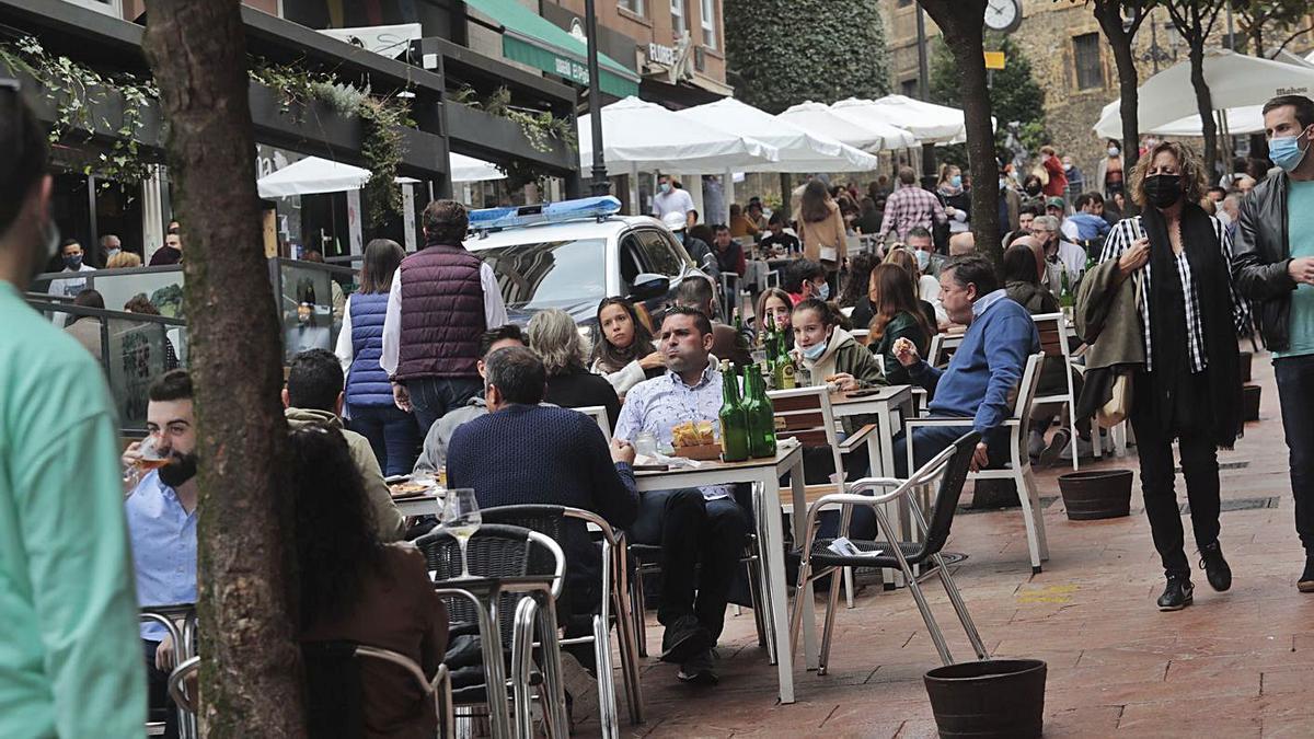 Un vehículo policial, entre las terrazas abarrotadas en Gascona, en el centro de Oviedo, al mediodía de ayer.   M. López
