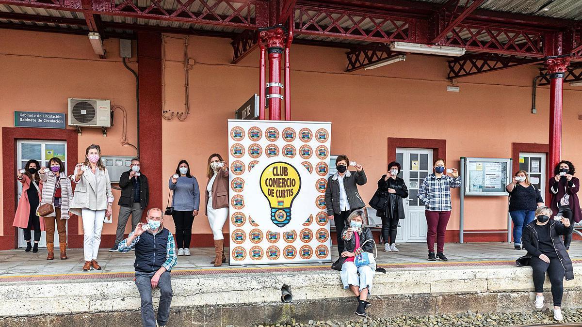 Los comerciantes de Curtis adheridos al sistema de fidelización posan con las tarjetas en la estación de tren.  | // LAURA MÍGUEZ