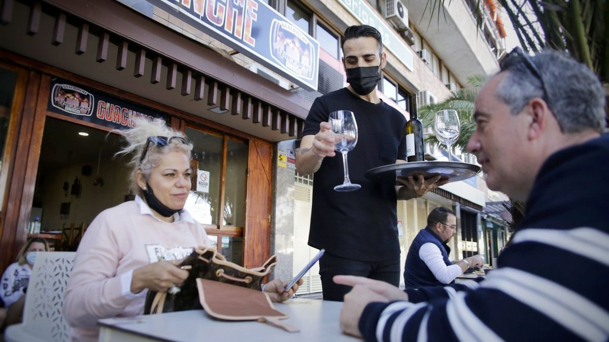 Un camarero atiende a dos clientes en una terraza de Santa Cruz.