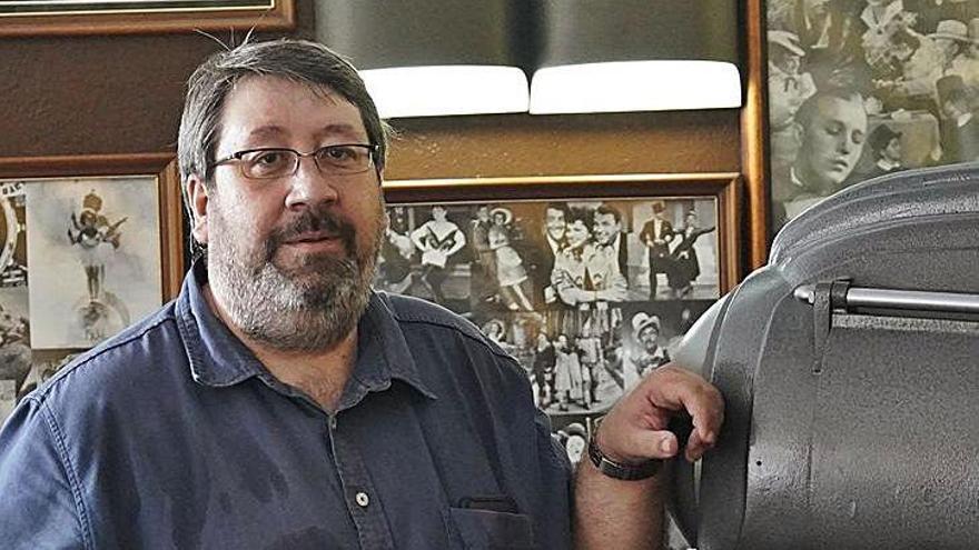 Carles Samada amb un projector antic que s'exhibeix al vestíbul de l'establiment.