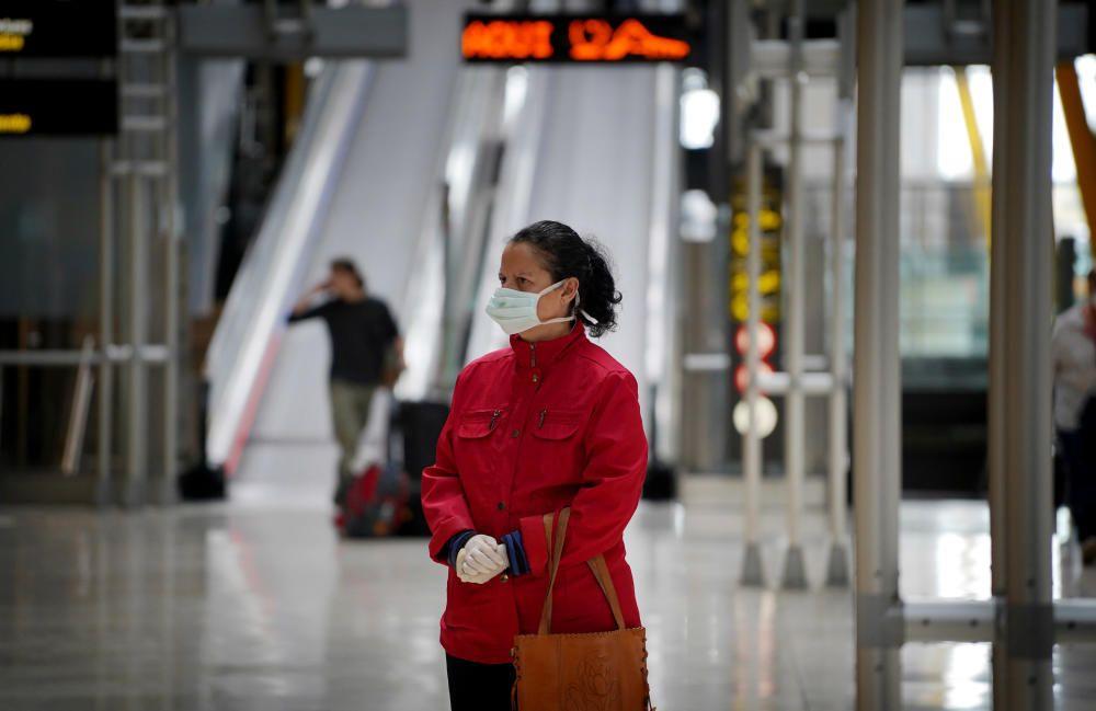 MADRID. 19.03.2020. CORONAVIRUS. Miembros de la UME limpian el aeropuerto de Barajas, terminal T4. En la imagen una mujer con mascarilla. FOTO: JOSE LUIS ROCA