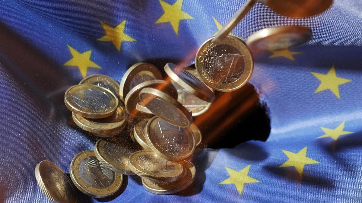 Monedas de euro sobre la bandera de la UE.