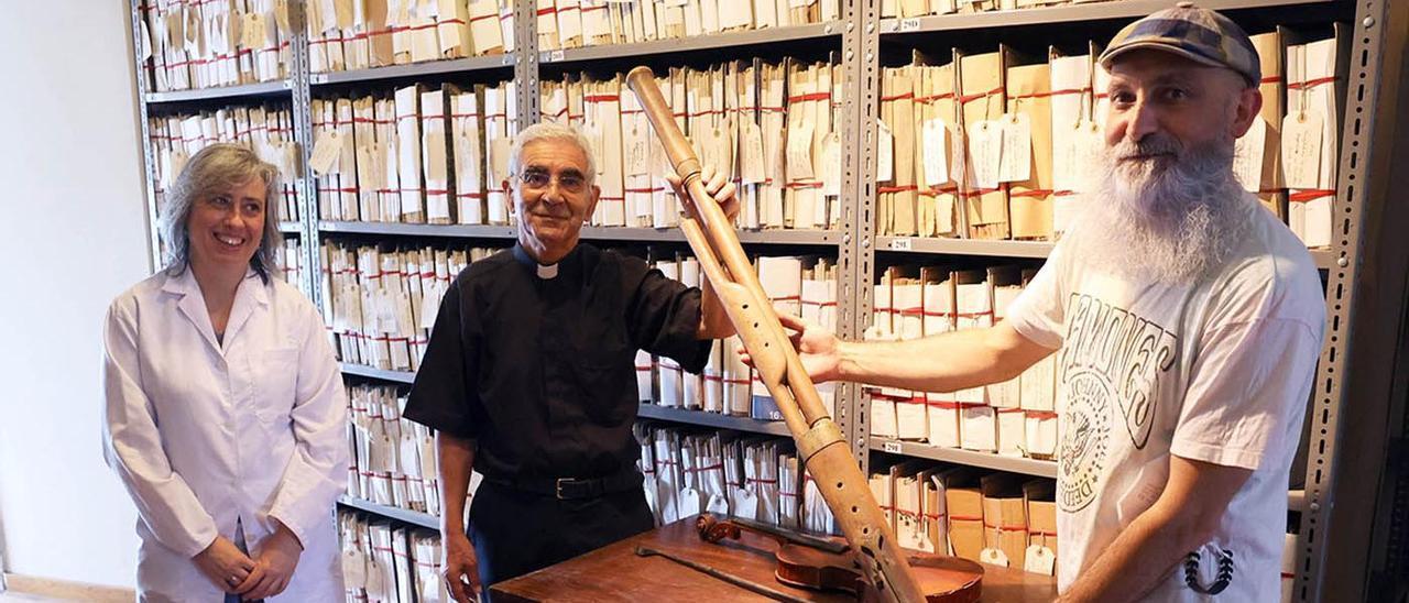 Avelino Bouzón y Oli Xiráldez (d.) muestran el fagot en presencia  de Macarena Cuiñas (i.) en el archivo de la Catedral de Tui.