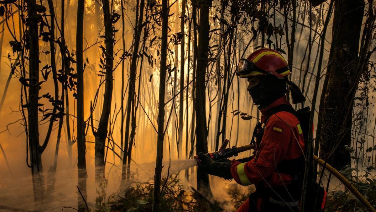 Un militar de la UME colabora en la extinción del incendio de Toén (Ourense). // Brais Lorenzo