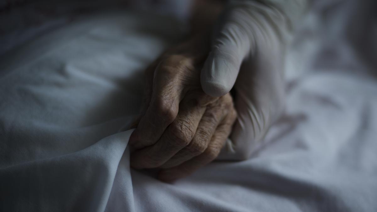 Una enfermera sujeta la mano de un paciente de COVID.