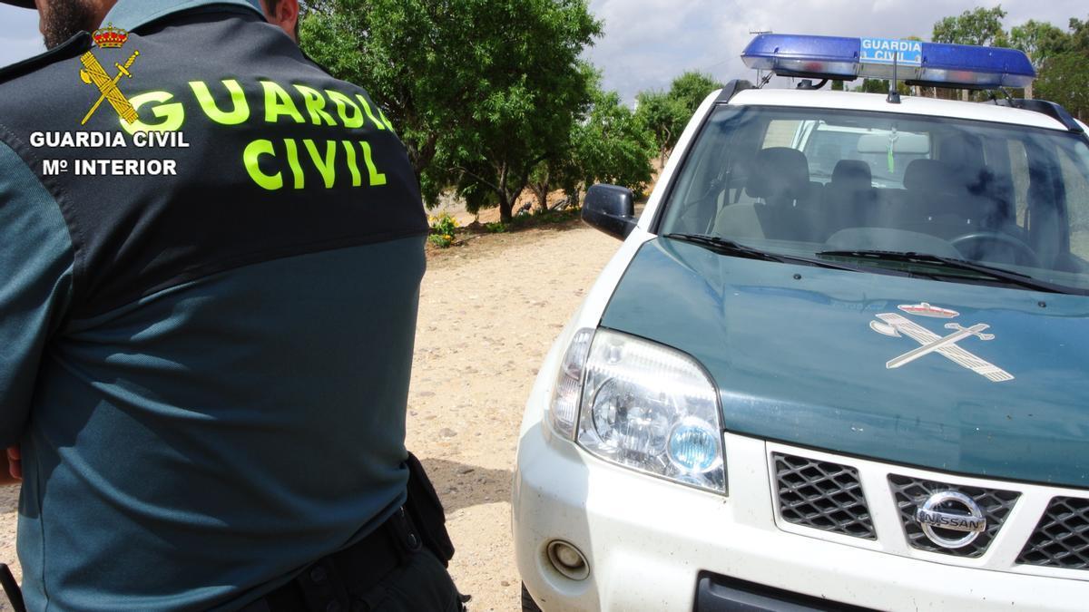 Archivo - Agente de la Guardia Civil junto a su vehículo