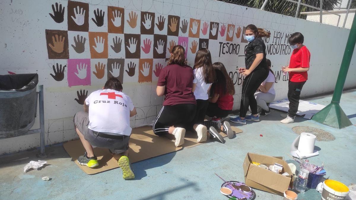 Los alumnos trabajan en la realización del mural sobre los refugiados.