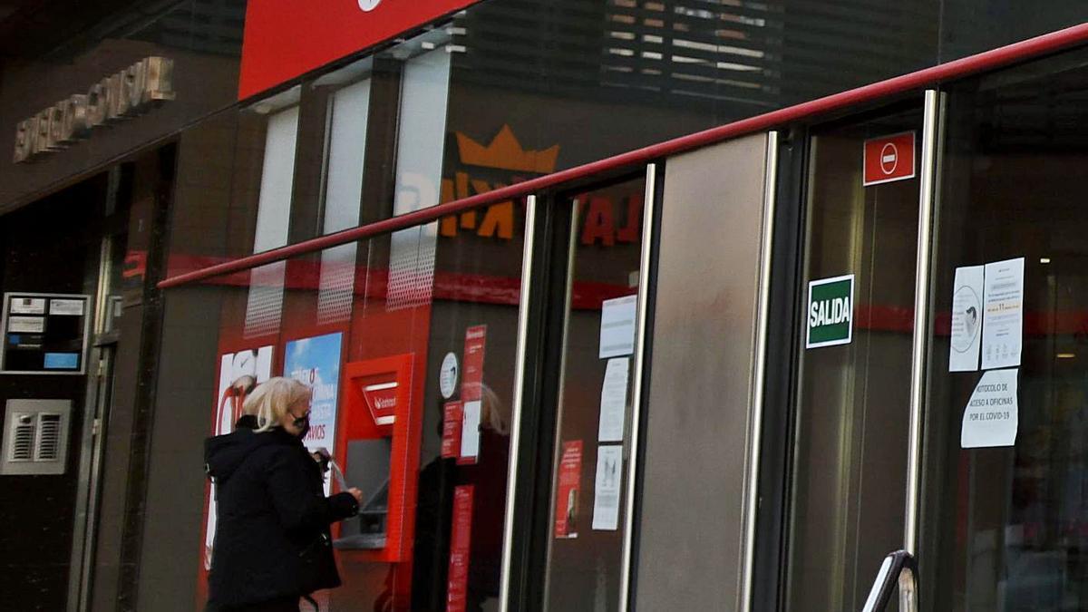 Una persona saca dinero de un cajero automático.   ISRAEL SÁNCHEZ