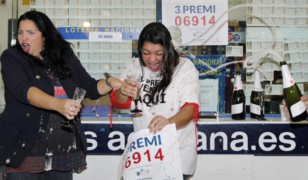 La dueña de la administración sita en las galerías Diagonal Mar de Barcelona Anabel Morales (i), brinda con su empleada Valeria Álvarez, tras repartir la suerte con el número 06914, agraciado con el tercer premio de la Lotería de Navidad. EFE