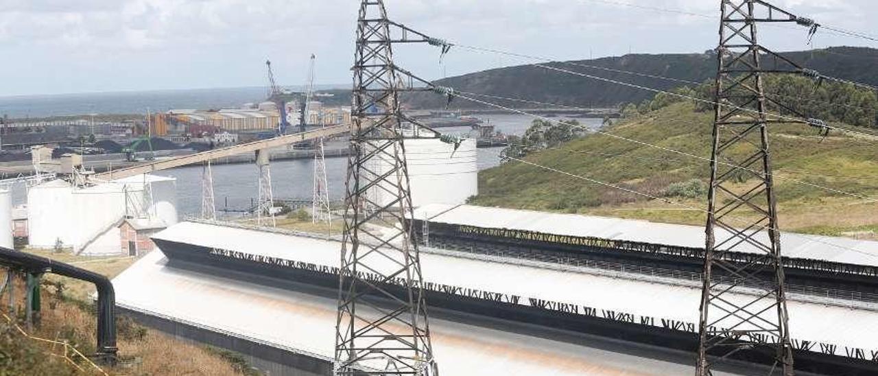 Dos torres eléctricas, en primer término, junto a las instalaciones de Alcoa en Avilés.