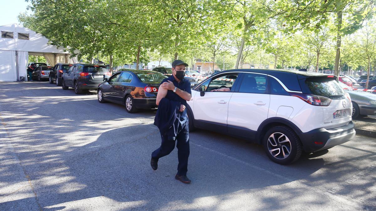 Un hombre pasea al lado de una fila de coches donde sus conductores esperan para ser vacunados en Ponferrada.