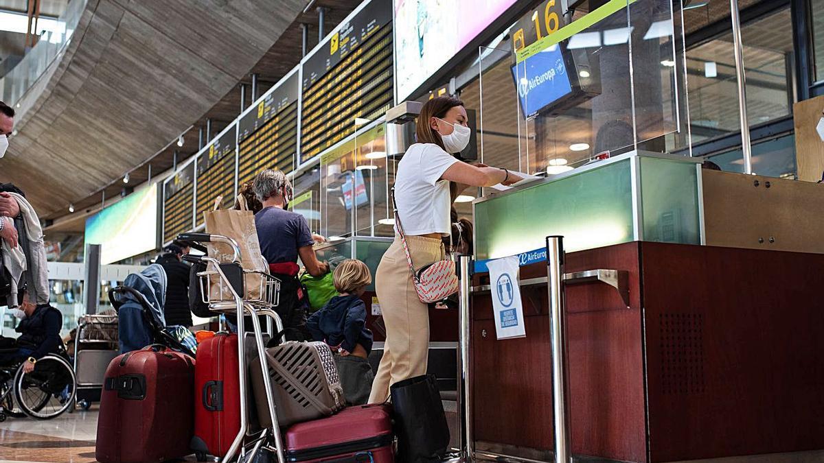 Una pasajera entrega documentación en el mostrador de facturación.