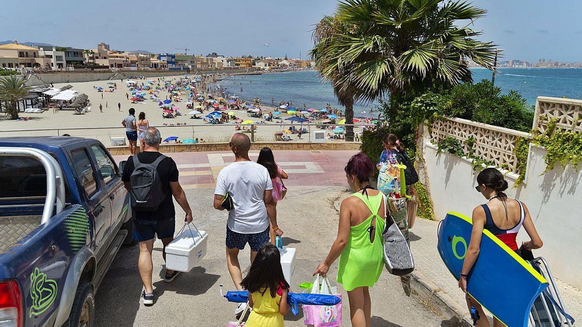 Varios veraneantes llegan hasta una de las playas de La Manga, llenas estos días de turistas.