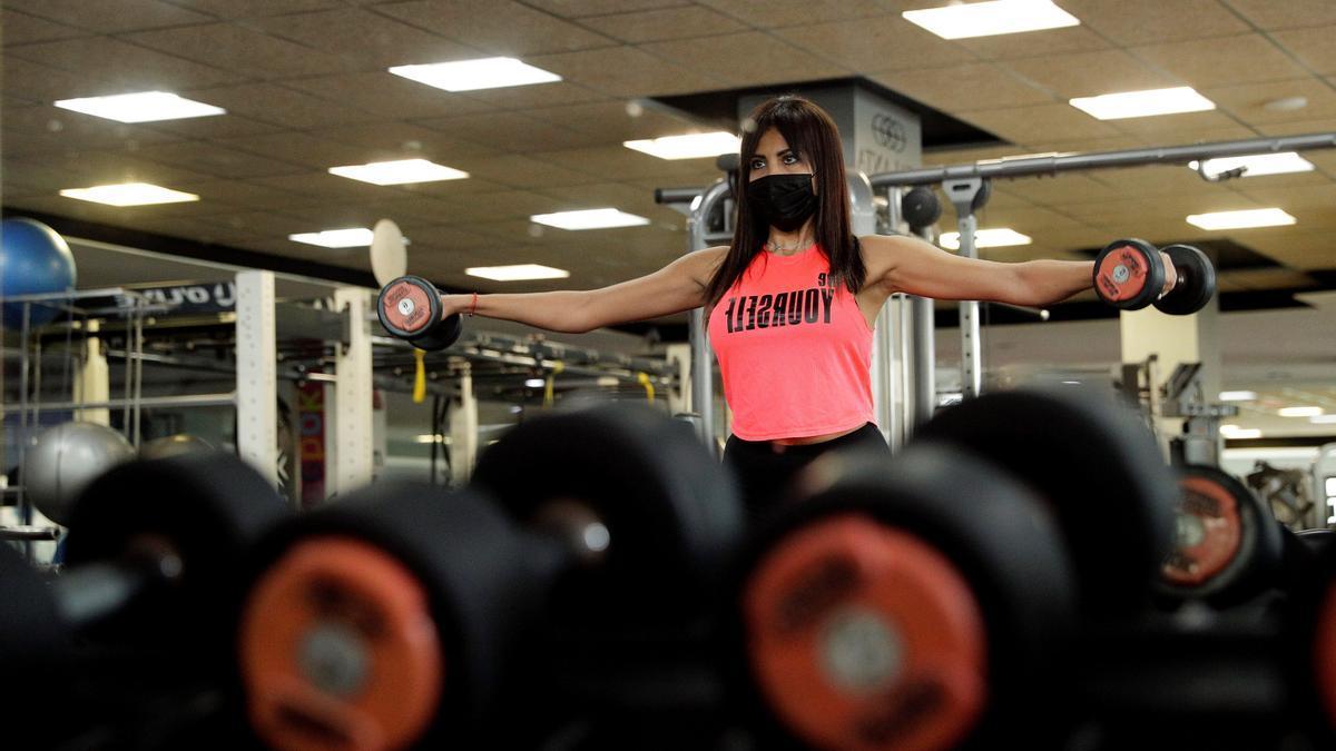 Una mujer entrena en un gimnasio.