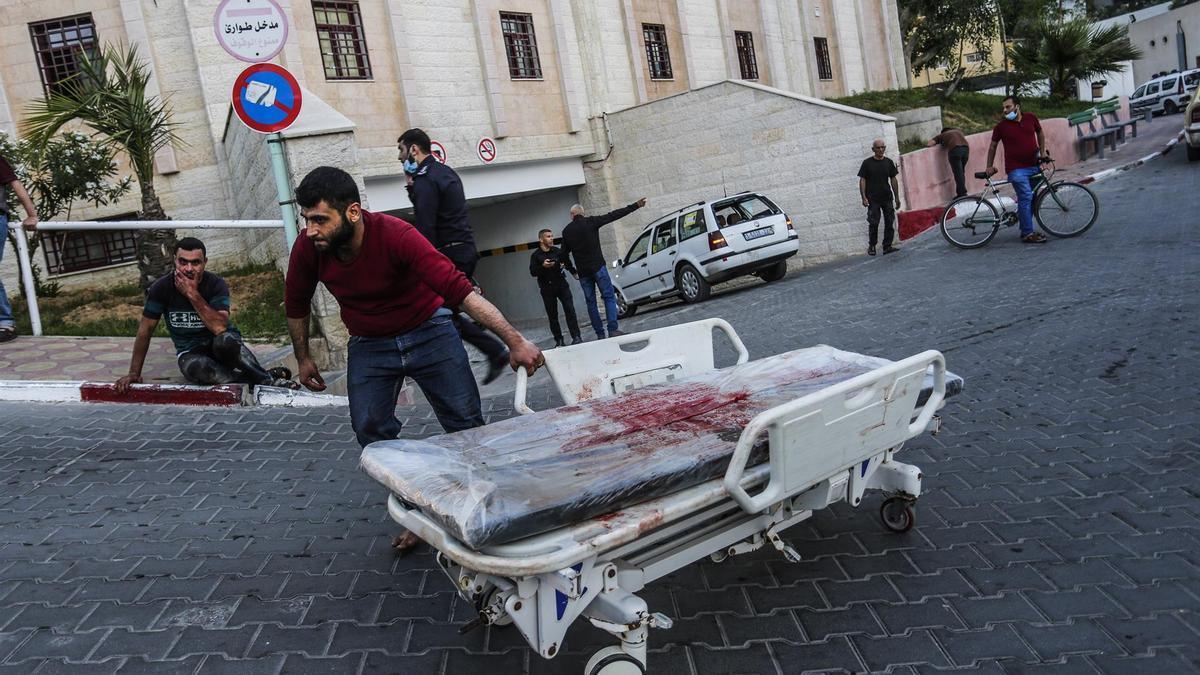 Un hombre palestino rueda una cama de hospital manchada de sangre en un hospital en el norte de la Franja de Gaza.