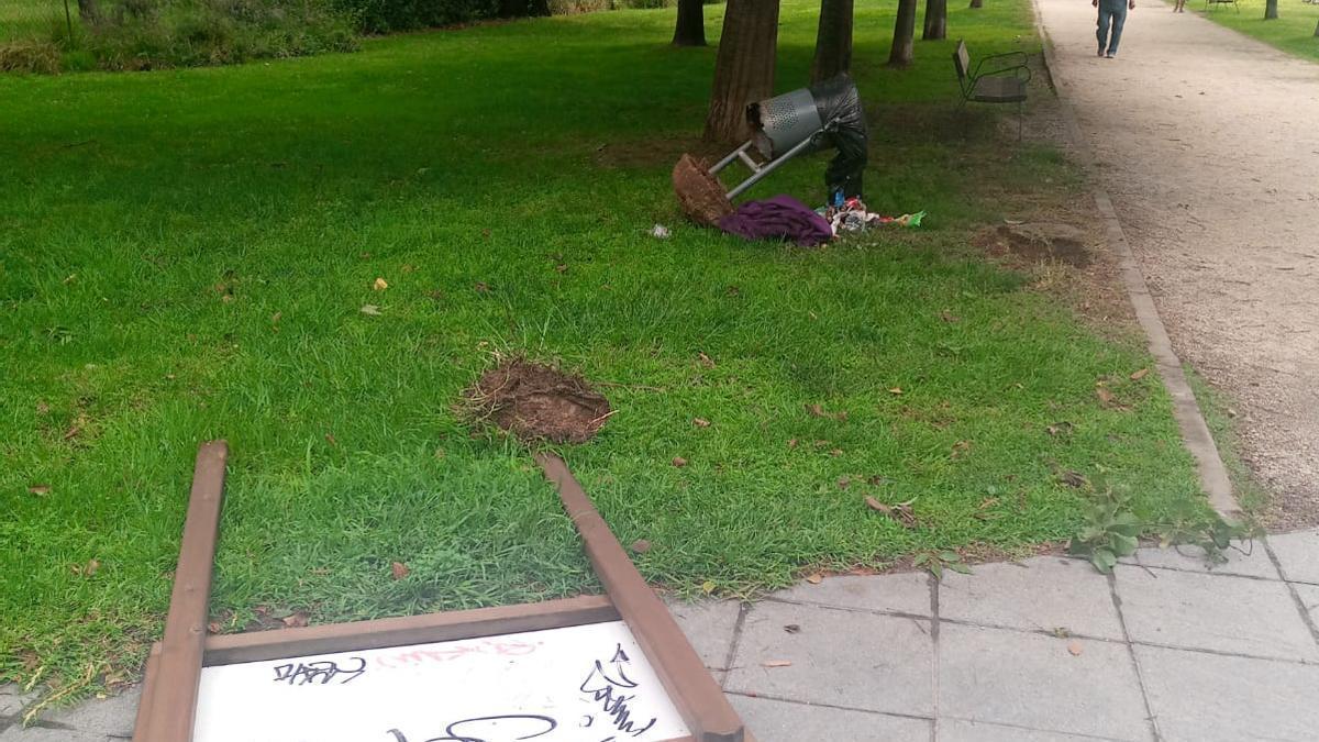 Cartel y papelera tumbados, este lunes en el parque de La Isla.