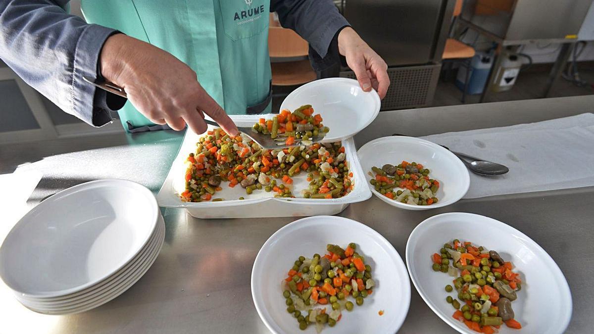 Una trabajadora sirve comida en un comedor escolar.     // GUSTAVO SANTOS
