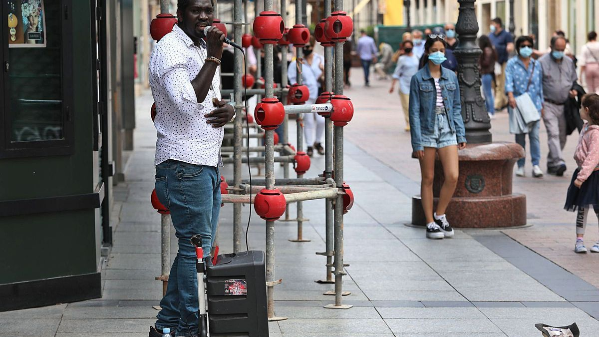 Un cantante callejero actúa en la calle Alfonso I de la capital aragonesa hace unos días.   ÁNGEL DE CASTRO