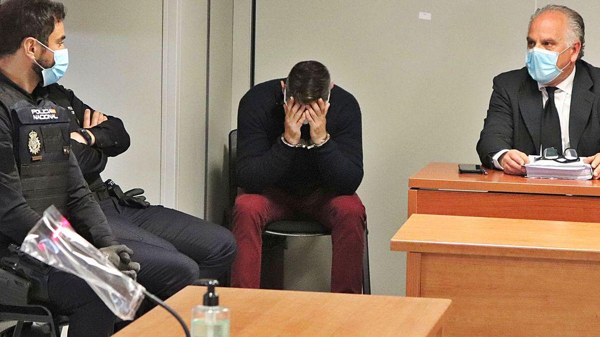 El acusado de matar a martillazos a un amigo se tapa el rostro con las manos.