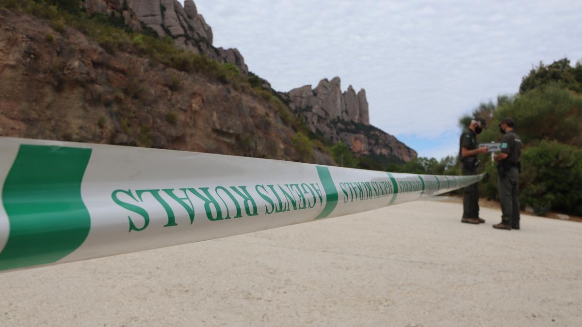 En primer terme, una cinta dels Agents Rurals tallant l'accés al Parc Natural de Montserrat. 13 de juliol de 2021. (Horitzontal)