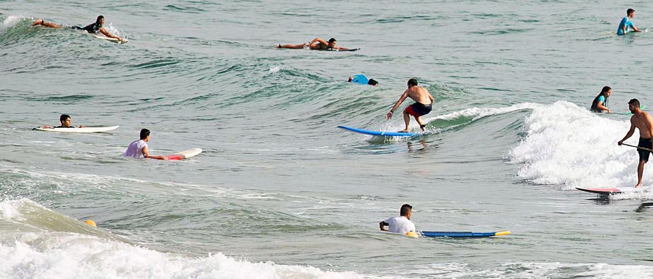 Surfistas en la playa de San Juan de Alicante -arriba- y en los Arenales de Elche -abajo-.   JOSE NAVARRO / MATÍAS SEGARRA