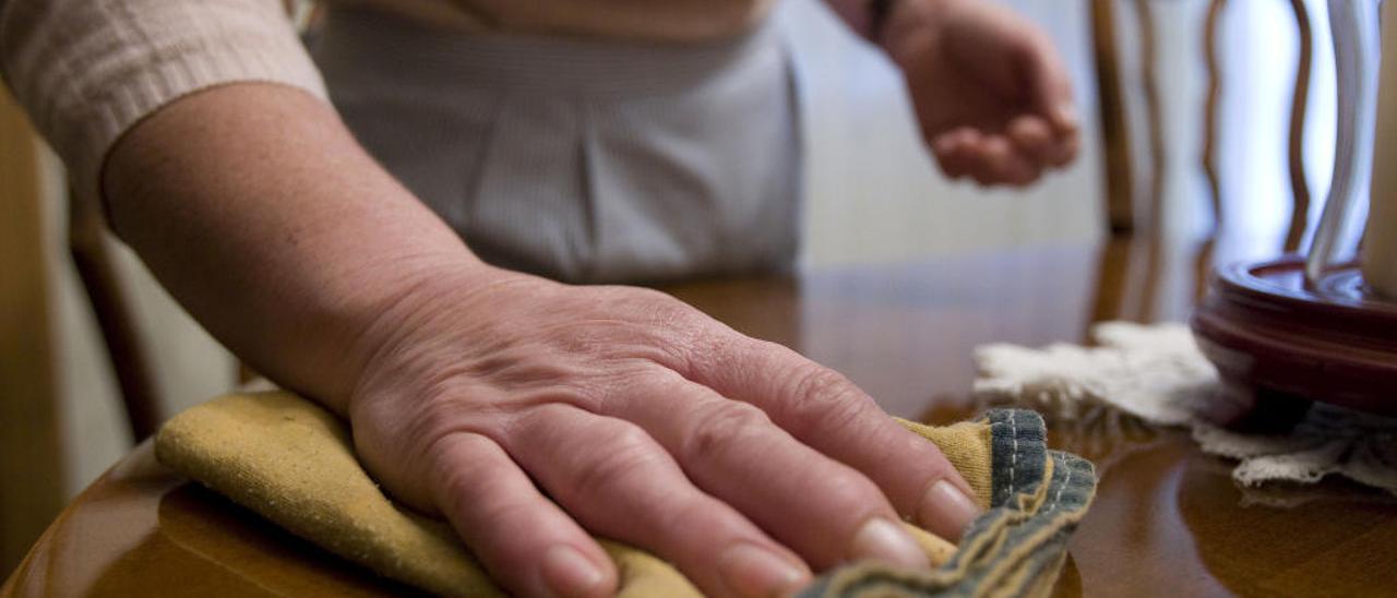 Imagen de archivo de una mujer haciendo las tareas de limpieza en el salón de una vivienda