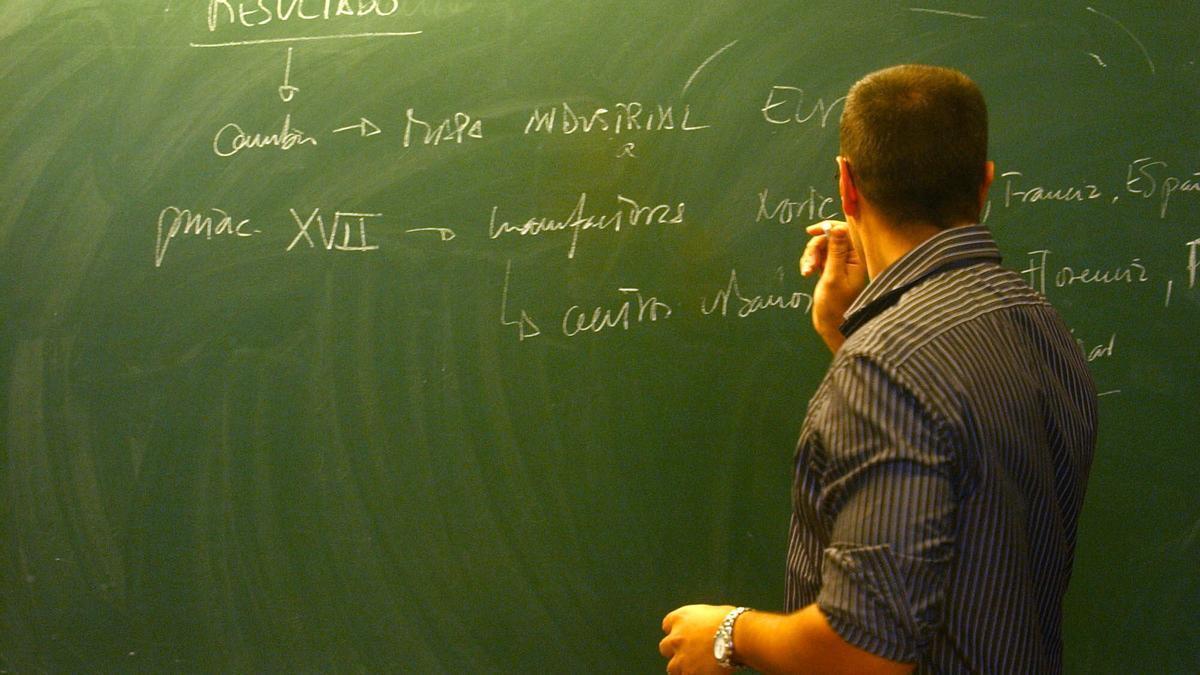 Un profesor escribe en el encerado de un aula gallega.