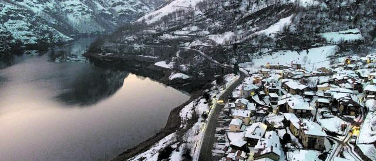 El pantano de Tanes, con las casas de la localidad a la derecha, tras las últimas nevadas. | Javier Gutiérrez