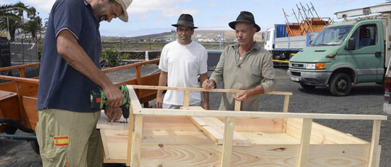 Onofre Martín (izquierda), Leandro de León y Juan José Álvarez ayer preparando los últimos carros para la romería de Los Dolores del sábado.