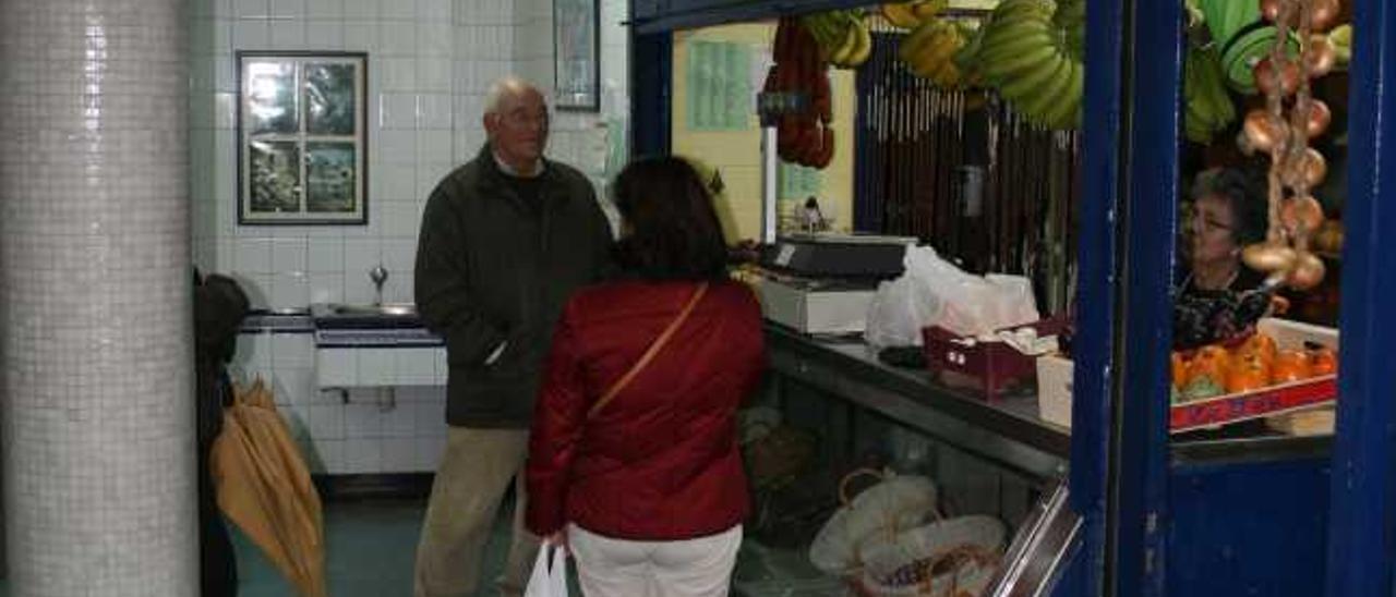 Clientes en una de las fruterías de la plaza de abastos de Candás.